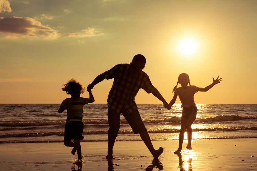 Grandfather and two granddaughters, playing on a beach at sunset.
