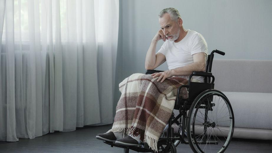 Sad looking senior man sitting in wheelchair.